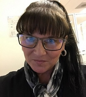 Woman with dark hair and black-rimmed glasses looks at the camera in an office environment